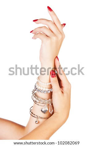 closeup hands of young woman with red manicure polished nails wearing many silver bangles and pearl bracelets - stock photo