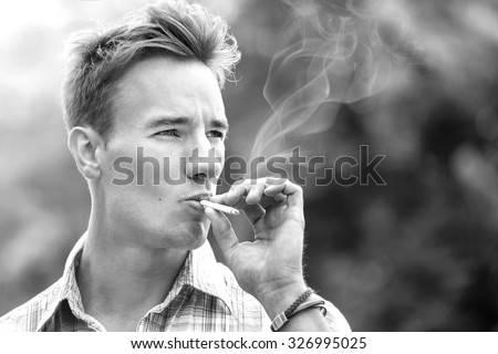 Closeup handsome young man smoking cigarette outdoors. Lens flare. Soft focus. Black and white