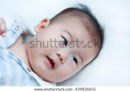 Closeup happy little baby smiling while lying in bed. A four months adorable baby girl, on white background. Positive human emotion. Studio shot. - stock photo