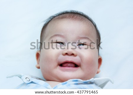 Closeup happy little baby smiling while lying in bed. Adorable baby girl, on white background. Positive human emotion. Studio shot. - stock photo