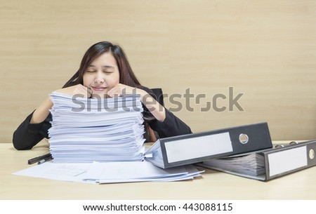 Closeup happy working woman sleeping after she finish her work with work paper and document file on blurred wooden desk and wall textured background in the meeting room , woman love her work concept
