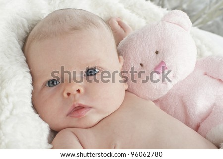 Closeup head and shoulders portrait of a contented beautiful bright-eyed new baby with light pink teddy bear. White fake fur blanket in soft focus background, horizontal layout.