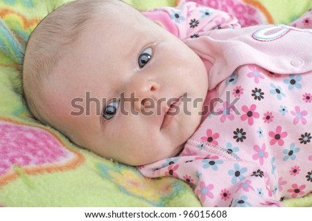 Closeup head and shoulders portrait of a new baby with clothing and blanket in pastel spring colors. Horizontal layout.