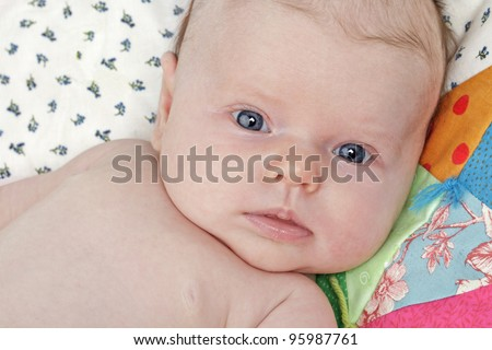 Closeup head and shoulders portrait of an alert, healthy, beautiful bright-eyed new baby. Colorful dainty patchwork quilt background, horizontal layout.