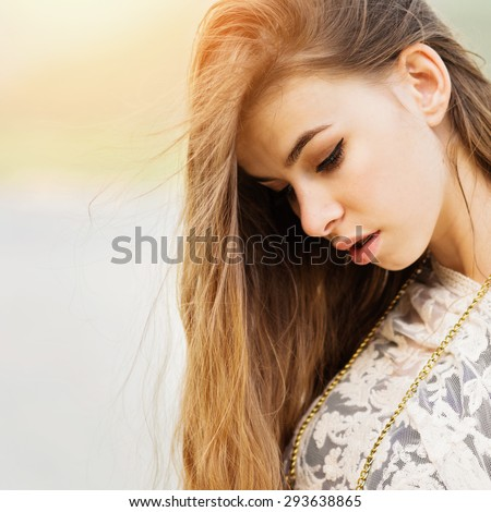 Closeup head shot of gorgeous young woman at the beach. Beautiful girl with long blonde hair looking down wearing makeup and sheer beige dress. Square format, retouched, vibrant colors. - stock photo