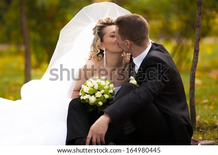 Closeup head shot of newly married couple kissing at autumn park