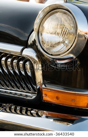 closeup headlight and grille of an old black classic car - stock photo