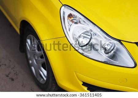 Closeup headlights of modern sport yellow car. Car exterior details - stock photo