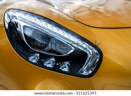 Closeup headlights of modern sport yellow car. Car exterior details. Closeup headlights of car. Modern luxury car close-up banner background. Concept of expensive, sports auto Closeup headlights - stock photo