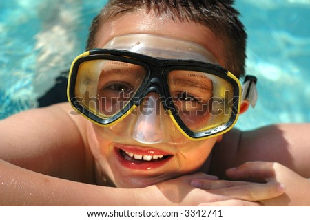 Closeup headshot of a kid in a diving mask having summer fun in the cool, clear water - stock photo
