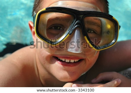 Closeup headshot of a kid in a diving mask having summer fun in the pool - stock photo