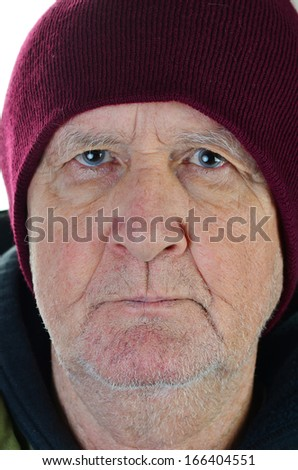 Closeup -- headshot of old man with beard stubble wearing stocking cap looking homeless and staring fearlessly into camera lens.
