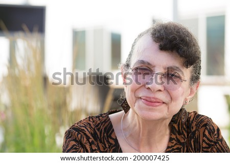 Closeup headshot portrait, grandmother with glasses, smiling, isolated outdoor background - stock photo