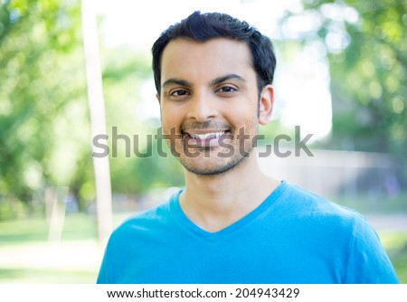 Closeup headshot portrait, happy handsome business man in blue shirt, relaxing outside nature scene during sunny day, isolated on green trees background - stock photo