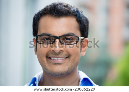 Closeup headshot portrait, happy handsome businessman, wearing black glasses relaxing outside of his office during sunny day, isolated on a blurred city urban background.  - stock photo