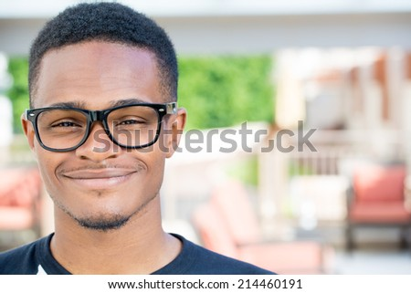 Closeup headshot portrait of fine young man with big glasses, undergrad student, smiling, isolated on outside outdoors background. - stock photo