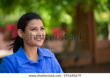 Closeup headshot portrait young beautiful happy business woman in blue shirt, sitting on bench, isolated green trees, nature background. Positive human emotion facial expression feelings - stock photo