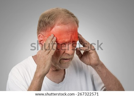 Closeup headshot senior man suffering from headache hands on head with red colored inflamed areas looking down isolated on gray wall background. Human face expression. Health problems issues - stock photo