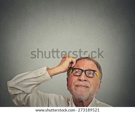 Closeup headshot undecided senior man with glasses scratching head thinking looking up isolated gray wall background with copy space. Human face expression emotion perception  - stock photo
