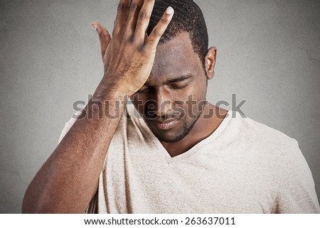 Closeup headshot very sad depressed, stressed, alone, disappointed gloomy young man head on hands having suicidal thoughts isolated grey wall background. Human emotion facial expression reaction  - stock photo