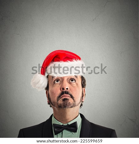 closeup headshot xmas man with red santa claus hat looking up at copy space on grey wall background thinking of gift idea for holiday.  Human face expression emotion perception reaction - stock photo