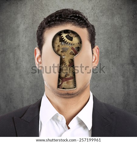 Closeup headshot young faceless man with keyhole and gear mechanism instead of face isolated on grey black texture office wall background  - stock photo