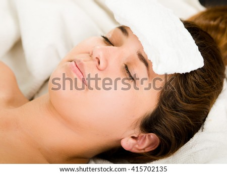 Closeup headshot young woman lying down with eyes closed, white towel pad resting on forehead