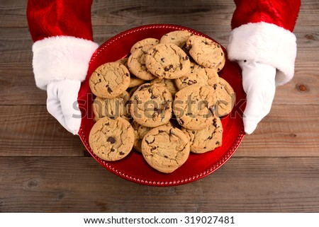Closeup high angle view of Santa Claus serving cookies. Only santa's hands are shown as he holds a red tray filled with chocolate chip cookies over a rustic wood table. - stock photo