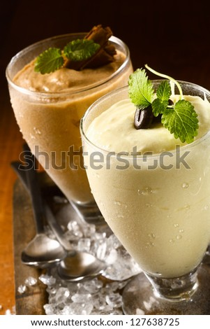 Closeup high angle view of two ice cold creamy double thick puddings or yoghurt dessert served in tall glasses garnished with chocolate on a bed of ice - stock photo