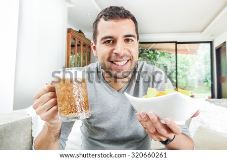 Closeup hispanic male wearing light blue sweater holding up beer and bowl of potato chips in front of camera, funny angle. - stock photo