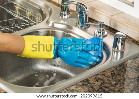 Closeup horizontal image of hand wearing rubber glove washing inside of kitchen sink with sponge and soapy water  - stock photo