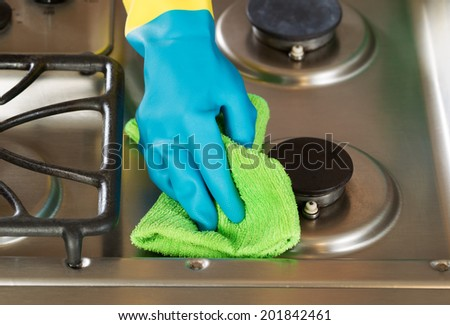 Closeup horizontal image of hand wearing rubber glove while cleaning stove top range with microfiber rag - stock photo