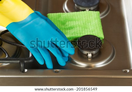 Closeup horizontal image of rubber gloves and microfiber rag on top of stove top range  - stock photo
