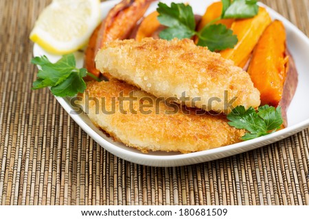Closeup horizontal of golden crisp fried fish and yams in white plate with bamboo place mat underneath  - stock photo
