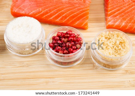 Closeup horizontal photo of dried red peppercorns with fresh Wild Red Salmon pieces in background  - stock photo