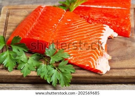 Closeup horizontal photo of fresh red salmon fillets on traditional wooden server with parsley on the side and rustic wood underneath  - stock photo