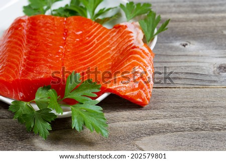 Closeup horizontal photo of fresh sockeye salmon fillet, partially out of plate, with parsley on the side and rustic wood underneath  - stock photo