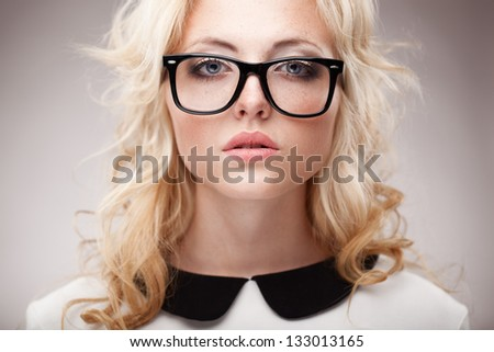 closeup horizontal portrait of blonde young beautifulwoman wearing eyeglasses - stock photo