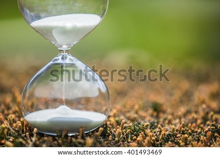 Closeup hourglass clock on colorful background - stock photo