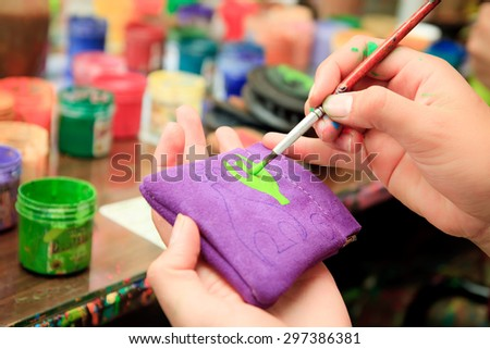 Closeup human hand painting a wallet with paintbrush, Traditional Otavalo Handcrafts market - stock photo