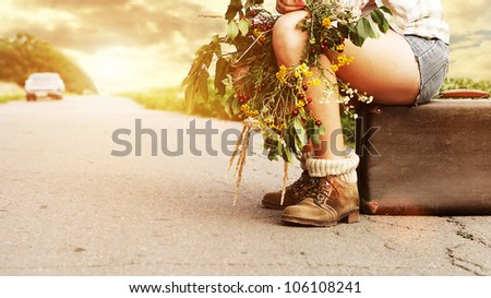 Closeup image auto stop traveler legs  and old suitcase at the sunset  on road - stock photo