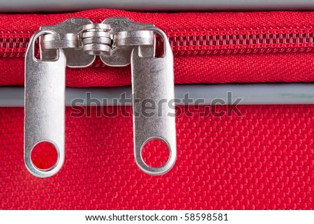 Closeup image from a closed zipper of a red suitcase - stock photo