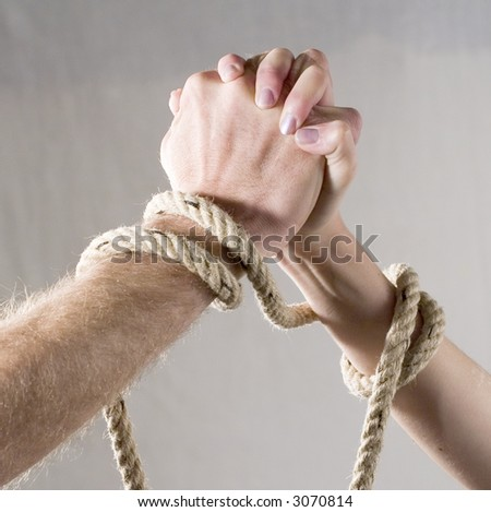 Closeup image from a woman's and a man's hand tied together - stock photo