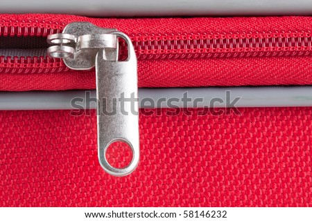 Closeup image from a zipper of a red suitcase half open
