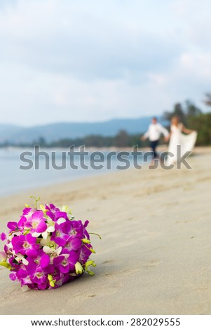 Closeup image of a bridal bouquet on a beach with couple in the background - stock photo