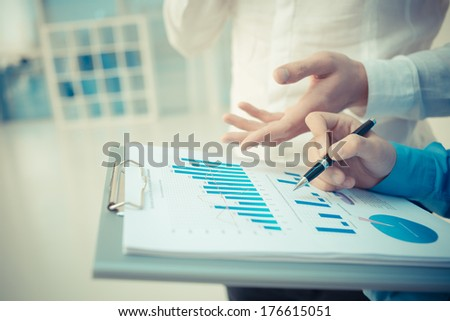 Closeup image of a business consultant explaining the financial aspects to the colleague on the foreground  - stock photo
