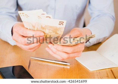 Closeup image of a businesswoman counting Euro bills over a wooden table.