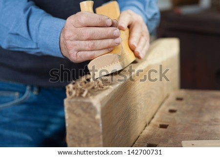 closeup image of a carpenter making something out of wood in the workshop. - stock photo