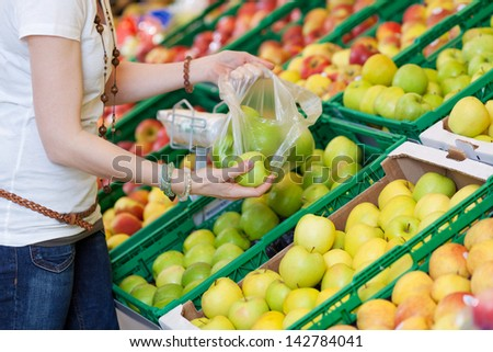 Closeup image of a female customer picking green apples to buy. - stock photo
