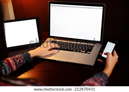 Closeup image of a female hands using smartphone and laptop - stock photo